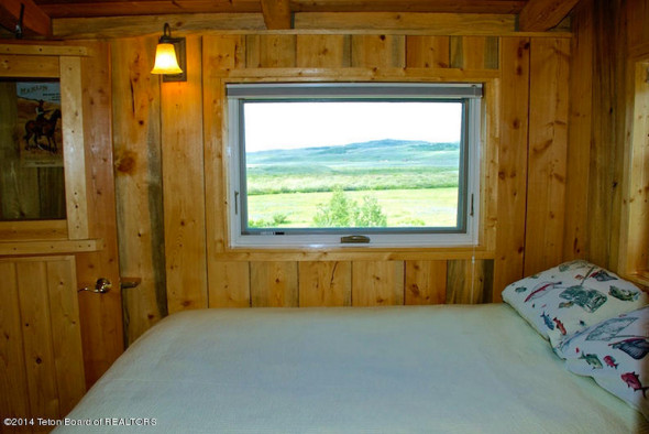 Charming little bedroom in tiny house log cabin for sale in Wyoming