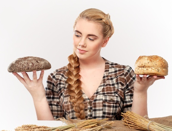 Woman Choosing Between Rye and Wheat Bread