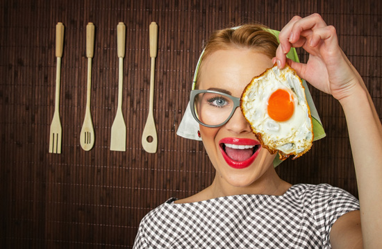 Woman Smiling and Holding a Fried Egg