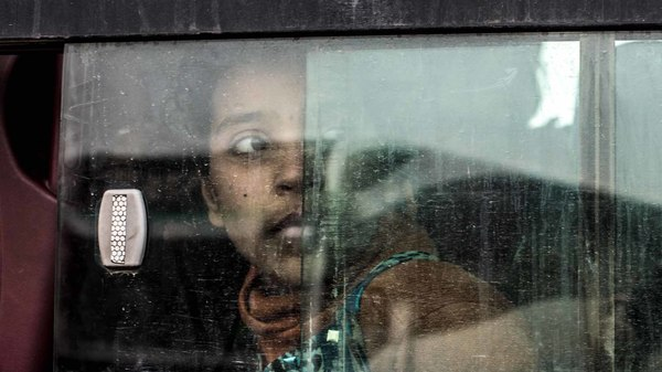 An Iraqi girl looks out the window of a bus transporting her to a nearby camp for internally displaced people.