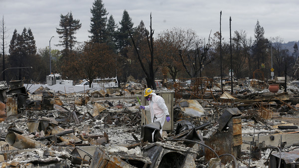 Work crews remove debris at the site of a home destroyed by fires in the Coffey Park area of Santa Rosa, Calif., last month. Thousands of homes and other structures were destroyed by wildfires in the area.