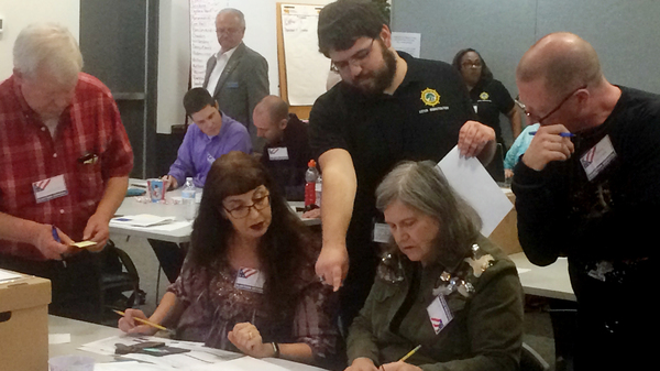 The results of the race between Republican incumbent David Yancey and Democratic challenger Shelly Simonds are still in doubt. Here, election officials in Newport News, Va., examine ballots that a computer failed to scan during a recount for their House of Delegates race on Dec. 19, 2017.