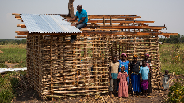 Twesigye Jackson Kaguri, in the blue t-shirt on the roof, helps build a home for a grandmother supported by his HIV/AIDS nonprofit in rural Uganda.