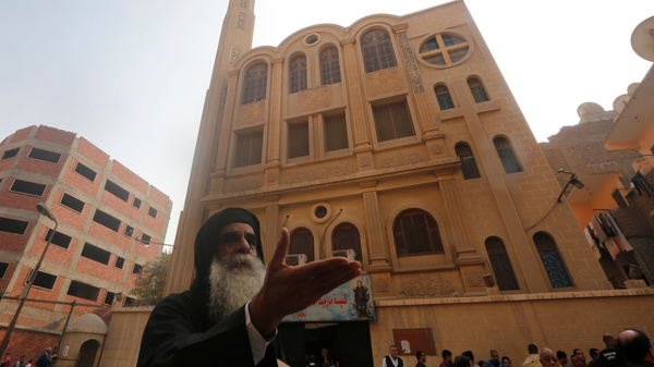 A priest reacts at the site of attack on a church in Helwan, south of Cairo, Friday. Officials say the attack killed at least nine people.