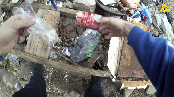 Body camera footage appears to show Officer Richard Pinheiro placing a can with drugs in a trash pile and returning later to seemingly discover it. A grand jury indicted him Tuesday.