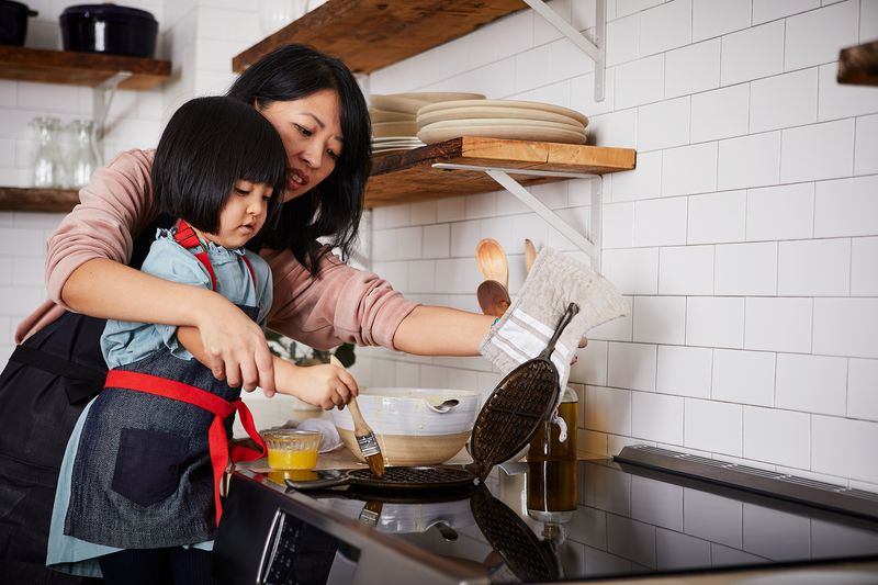 Hana and her daughter, Lana, making waffles together on an induction cooktop in the Food52 kitchen.
