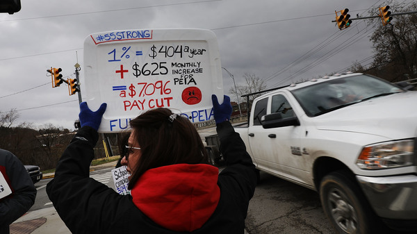 W. Va. teachers, students and supporters hold signs on a Morgantown, W. Va., street on Saturday. The strike is in its second weekend after the state Senate failed to pass the 5 percent raise teachers are demanding.