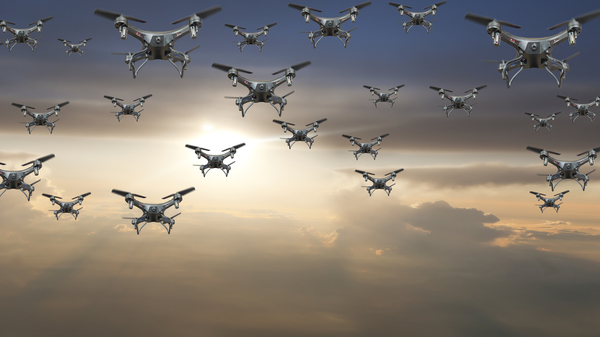 A flock of drones flying against a sunset. On Wednesday the Department of Transportation announced the launch of a pilot program that will lead to new regulations.