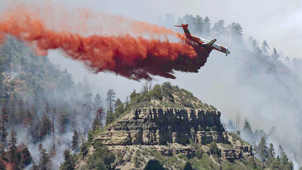 An airplane drops fire retardant on a fire outside of Durango, Colo. The 416 fire has forced 2,500 home evacuations.